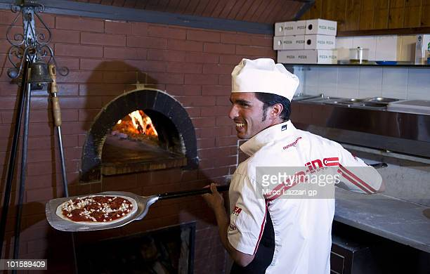 Toni Elias of Spain and Gresini Racing Moto2 prepares the Pizza in Pizzeria Il Rustico during the preevent 'Riders learn how to make pizza' during...