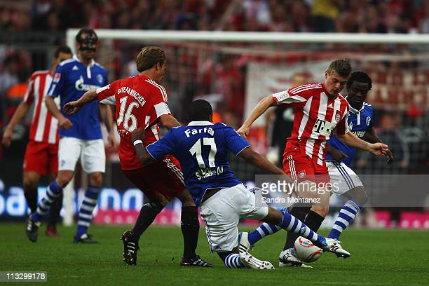 Toni Kroos of Bayern is challenged by Jefferson Farfan and Anthony Annan of Schalke during the Bundesliga match between FC Bayern Muenchen and FC...