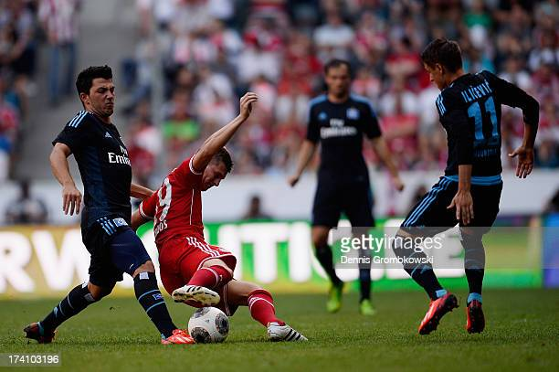 Toni Kroos of FC Bayern Muenchen is challengend by Tolgay Arslan and Ivo Ilicevic of Hamburger SV during the Telekom Cup 2013 semifinal match between...