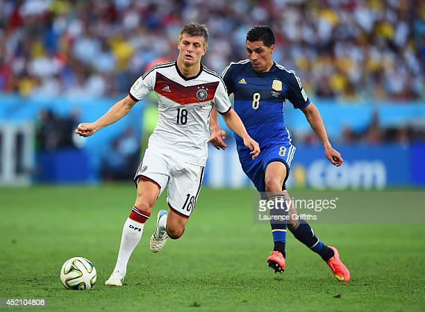 Toni Kroos of Germany and Enzo Perez of Argentina compete for the ball during the 2014 FIFA World Cup Brazil Final match between Germany and...