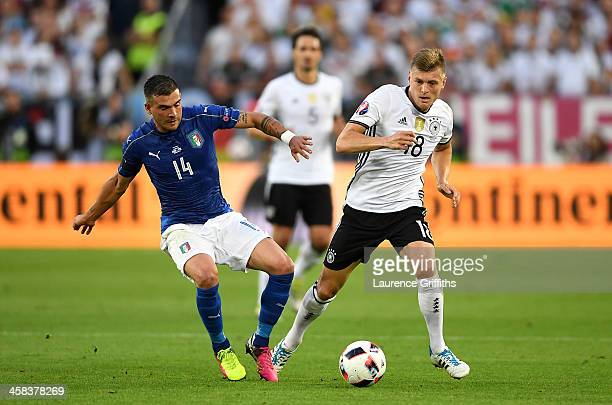 Toni Kroos of Germany and Stefano Sturaro of Italy compete for the ball during the UEFA EURO 2016 quarter final match between Germany and Italy at...