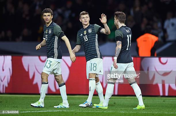 Toni Kroos of Germany celebrates scoring his team's first goal with his team mate Thomas Mueller and Marco Reus during the International Friendly...