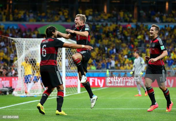 Toni Kroos of Germany celebrates scoring his team's fourth goal with his teammates Sami Khedira and Miroslav Klose during the 2014 FIFA World Cup...