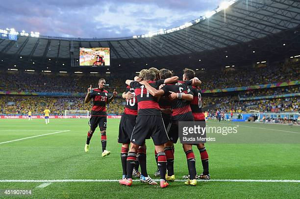 Toni Kroos of Germany celebrates scoring his team's fourth goal with his team-mates during the 2014 FIFA World Cup Brazil Semi Final match between...