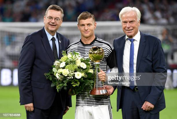 Toni Kroos of Germany is awarded the Germany Player of the Year award by Reinhard Grindel President of the German Football Association and Rainer...