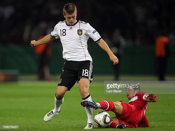 Toni Kroos of Germany is challenged by Emre Beloezoglu of Turkey during the EURO 2012 Group A qualifier match between Germany and Turkey at Olympic...