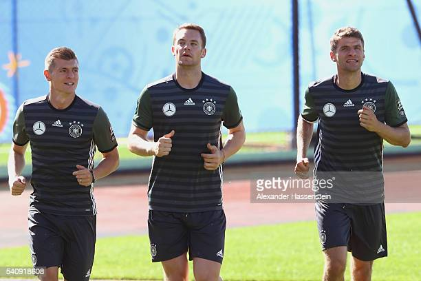 Toni Kroos of Germany runs with his team mates Manuel Neuer and Thomas Mueller during a Germany training session at Ermitage Evian on June 17 2016 in...