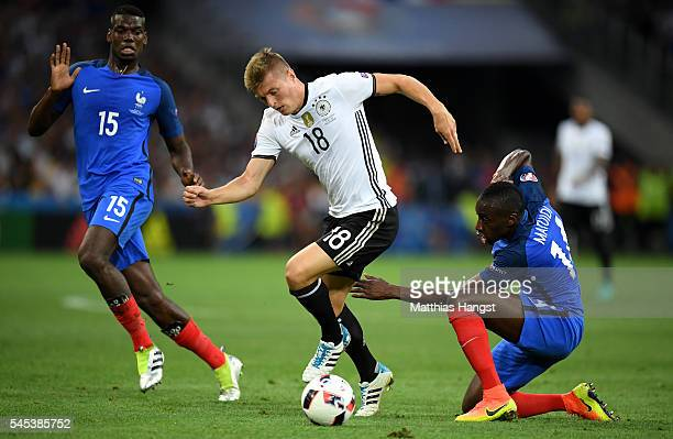 Toni Kroos of Germany runs wituh the ball under pressure from Blaise Matuidi and Paul Pogba of France during the UEFA EURO semi final match between...