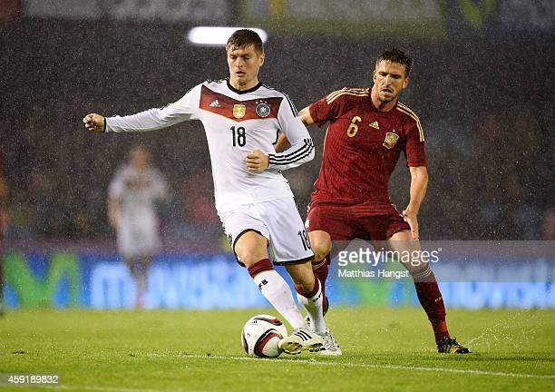 Toni Kroos of Germany vies with Ignacio Camacho of Spain during the International Friendly match between Spain and Germany at Estadio Balaidos on...