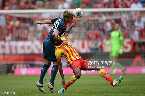 Toni Kroos of Muenchen competes with Alex Song of Barcelona during the Uli Hoeness Cup match between FC Bayern Muenchen and FC Barcelona at Allianz...