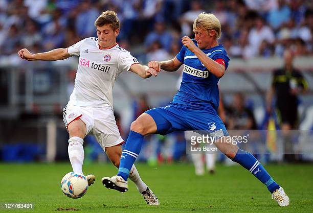 Toni Kroos of Muenchen is challenged by Andreas Beck of Hoffenheim during the Bundesliga match between 1899 Hoffenheim and FC Bayern Muenchen at...