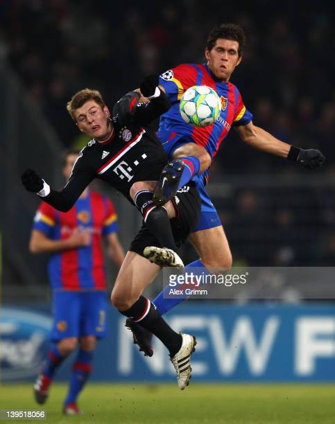 Toni Kroos of Muenchen is challenged by Benjamin Huggel of Basel during the UEFA Champions League Round of 16 first leg match between FC Basel 1893...