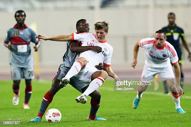 Toni Kroos of Muenchen is challenged by Tresor Kangambu of Lekhwiya during the international friendly match between Lekhwiya Sports Club and FC...