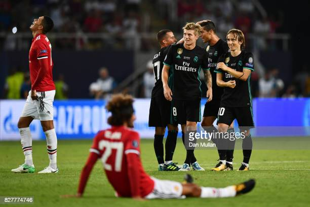 Toni Kroos of Real Madrid and Luka Modric of Real Madrid celebrate victory as Marouane Fellaini of Manchester United is dejected after the UEFA Super...