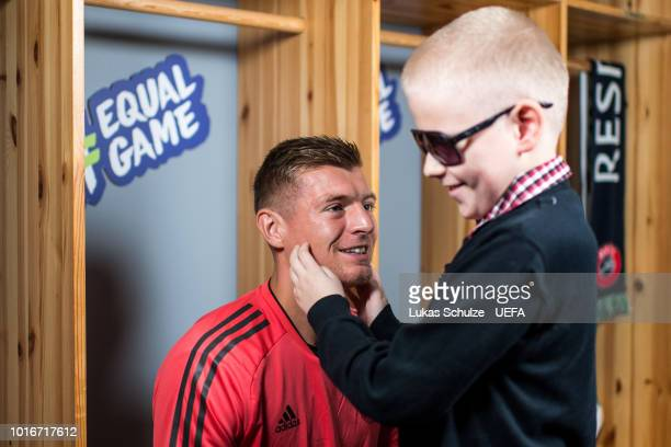 TALLINN ESTONIA AUGUST Toni Kroos of Real Madrid and the blind boy Aron Leppik of the UEFA Foundation talk to each other ahead of Atletico Madrid's...