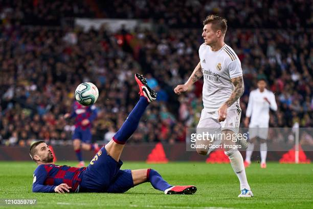 Toni Kroos of Real Madrid CF battle for the ball with Gerard Pique of FC Barcelona during the Liga match between Real Madrid CF and FC Barcelona at...
