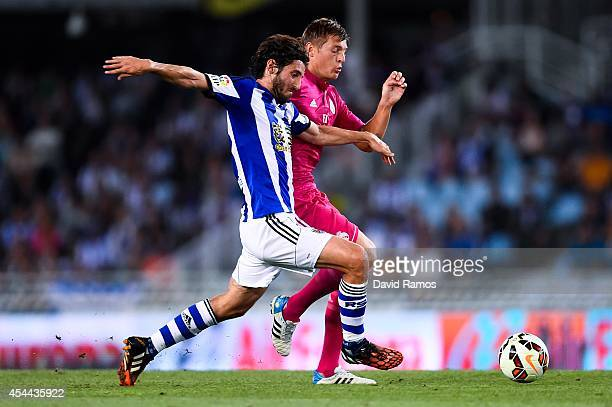 Toni Kroos of Real Madrid CF competes for the ball with Esteban Granero of Real Sociedad during the La Liga match between Real Sociedad de Futbol and...