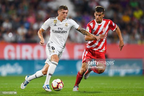 Toni Kroos of Real Madrid CF competes for the ball with Pere Pons of Girona FC during the La Liga match between Girona FC and Real Madrid CF at...