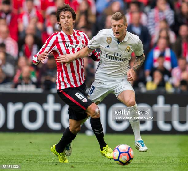Toni Kroos of Real Madrid competes for the ball with Ander Iturraspe of Athletic Club during the La Liga match between Athletic Club Bilbao and Real...