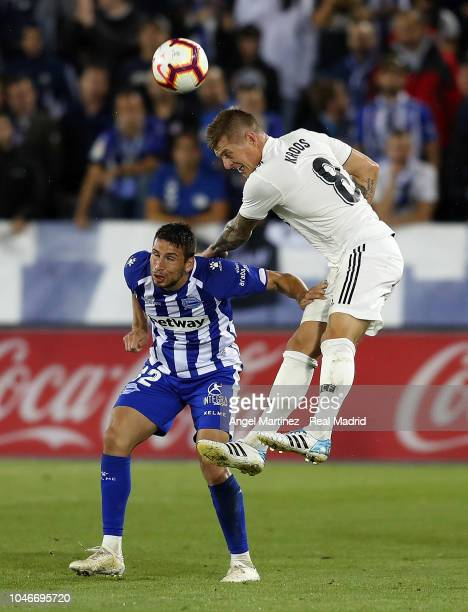 Toni Kroos of Real Madrid competes for the ball with Jonathan Calleri of Deportivo Alaves during the La Liga match between Deportivo Alaves and Real...