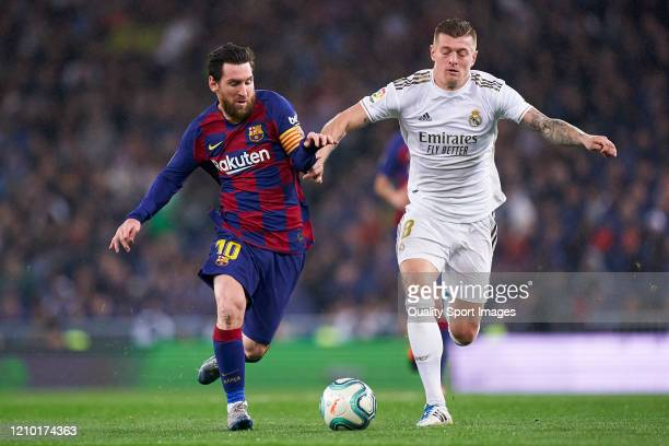 Toni Kroos of Real Madrid competes for the ball with Lionel Messi of FC Barcelona during the La Liga match between Real Madrid CF and FC Barcelona at...