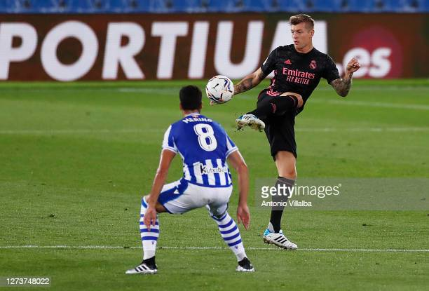 Toni Kroos of Real Madrid controls the ball under pressure from Mikel Merino of Real Sociedad during the La Liga Santander match between Real...