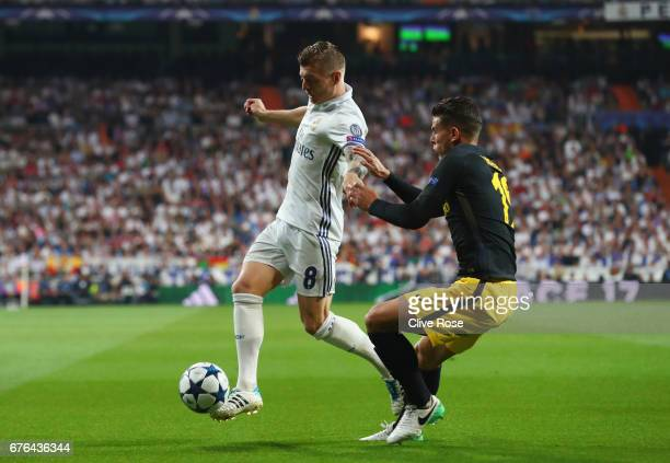 Toni Kroos of Real Madrid holds off Lucas Hernandez of Atletico Madrid during the UEFA Champions League semi final first leg match between Real...
