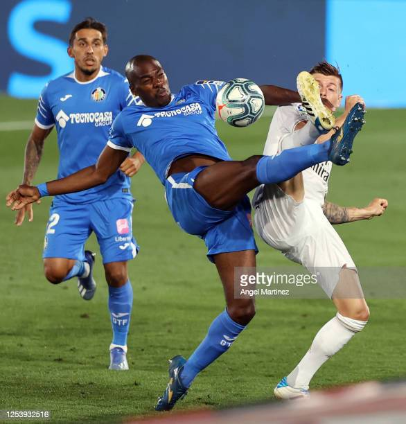 Toni Kroos of Real Madrid is challenged by Allan Nyom of Getafe during the Liga match between Real Madrid CF and Getafe CF at Estadio Alfredo Di...
