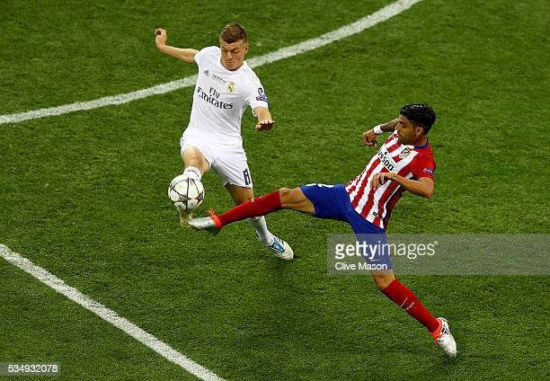 Toni Kroos of Real Madrid is challenged by Augusto Fernandez of Atletico Madrid during the UEFA Champions League Final match between Real Madrid and...