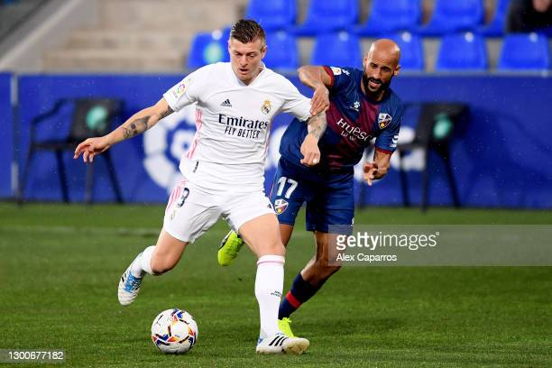 Toni Kroos of Real Madrid is challenged by Mikel Rico of SD Huesca during the La Liga Santander match between SD Huesca and Real Madrid at Estadio El...