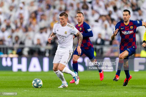 Toni Kroos of Real Madrid is chased by Sergio Busquets of FC Barcelona during the Liga match between Real Madrid CF and FC Barcelona at Estadio...