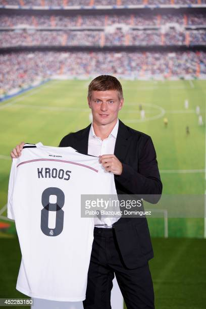 Toni Kroos poses for photographers with his new Real Madrid shirt during his official unveiling at Santiago Bernabeu Stadium on July 17 2014 in...
