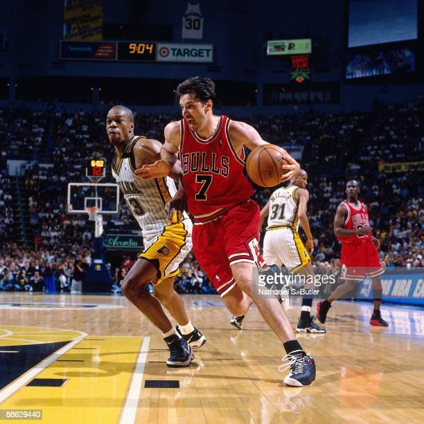 Toni Kukoc of the Chicago Bulls drives to the basket against Antonio Davis of the Indiana Pacers in Game Six of the Eastern Conference Finals during...