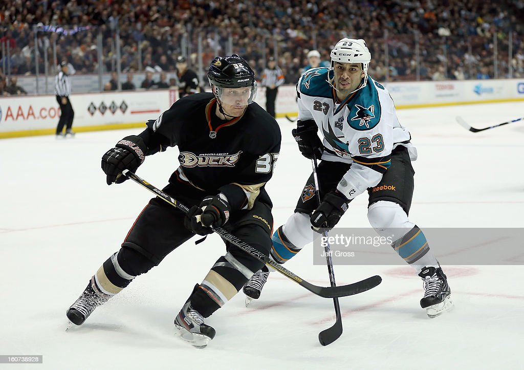 Toni Lydman #32 of the Anaheim Ducks and Scott Gomez #23 of the San Jose Sharks battle for position in the second period at Honda Center on February 4, 2013 in Anaheim, California. The Ducks defeated the Sharks 2-1.