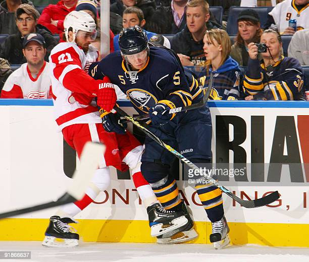 Toni Lydman of the Buffalo Sabres checks Ville Leino of the Detroit Red Wings on October 13 2009 at HSBC Arena in Buffalo New York