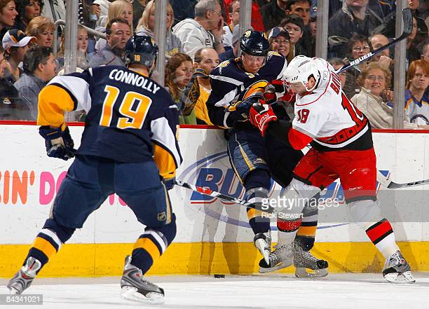 Toni Lydman of the Buffalo Sabres is checked off the puck by Ryan Bayda of the Carolina Hurricanes as Tim Connolly of the Sabres watches on January...