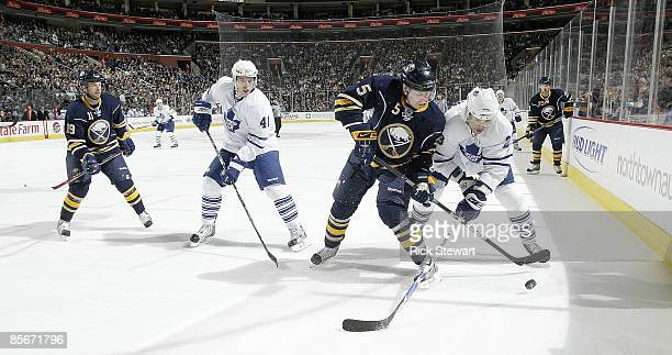 Toni Lydman of the Buffalo Sabres tries to get puck control from Alexei Ponikarovsky of the Toronto Maple Leafs as Tim Connolly of the Sabres and...