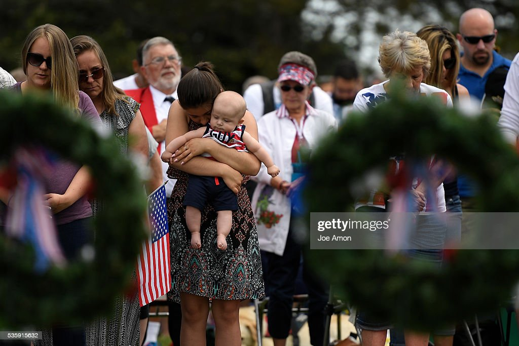Toni Munoz 14 hugging her 5 month old nephew Jace Coat during a prayer at the Memorial Day ceremony, 84th Anniversary of Remembrance at Fort Logan National Cemetery. Her dad Anthony Munoz died earlier this year he had served in the USMC and the Army reserve for 26 years. May 30, 2016 in Denver, CO.
