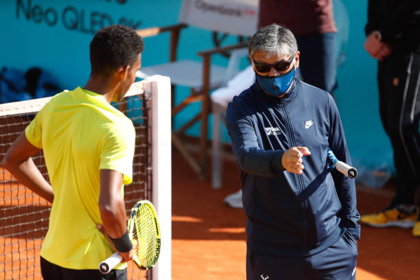 Toni Nadal, head coach, talks to Felix Auger-Aliassime of Canada during his practice on day two of the ATP Masters 1000 - Mutua Madrid Open 2021 at...