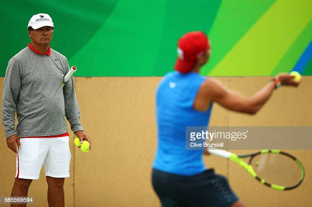Toni Nadal watches on as Rafael Nadal of Spain serves during a practice session ahead of the Rio 2016 Olympic Games at the Olympic Tennis Centre on...