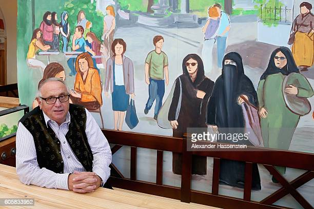 Toni Roiderer who runs the HackerPschorr tent at the 2016 Oktoberfest sits under a painting inside the tent that shows a woman in a burka and other...
