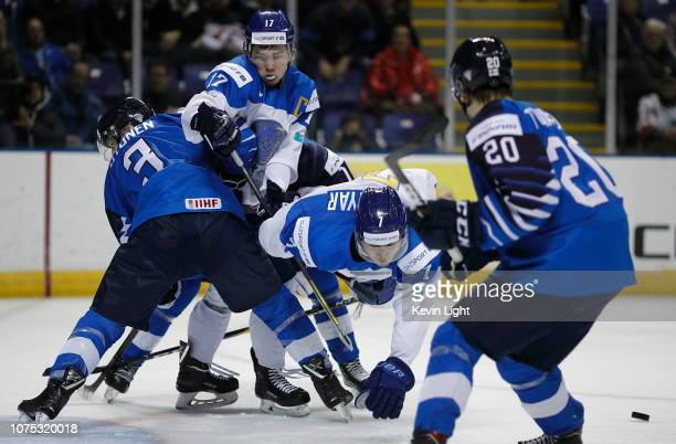 Toni Utunen of Finland checks Sayan Daniyar and Samat Daniyar of Kazakhstan at the IIHF World Junior Championships at the Save-on-Foods Memorial...