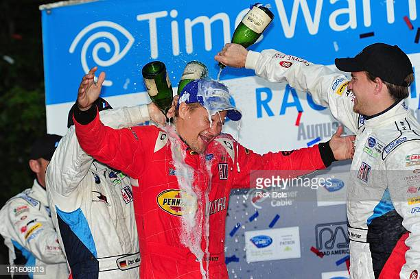 Toni Vilander of Finland and codriver of the Risi Competizione Ferrari 458 Italia is drenched on the podium during the American Le Mans Series Time...
