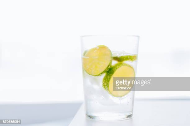 tonic water glass with slices of limes - tonic water stock pictures, royalty-free photos & images