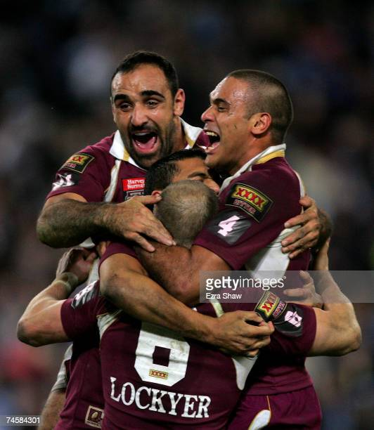 Tonie Carroll and Justin Hodges jump on Darren Lockyer of the Maroons after they beat the Blues in game two of the ARL State of Origin series between...
