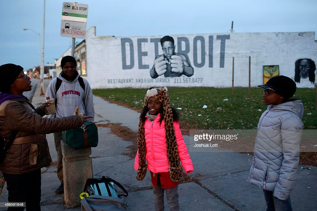 Tonja Boyd (L) talks with her daughters Nemyla Boyd (C) and Alexandria Boyd (R) as they wait at a bus stop November 7, 2014 in Detroit, Michigan. Today U.S. Bankruptcy Judge Steven Rhodes gave the City of Detroit the okay to plan an exit strategy from Chapter 9 Bankruptcy.