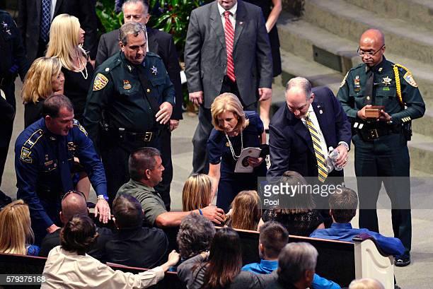 Tonja Garafola seated center widow of East Baton Rouge Sheriff deputy Brad Garafola is greeted by Louisiana Gov John Bel Edwards second right his...
