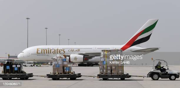 Tonnes of medical equipment and coronavirus testing kits provided bt the World Health Organisation are pictured passing by an Emirates airlines...