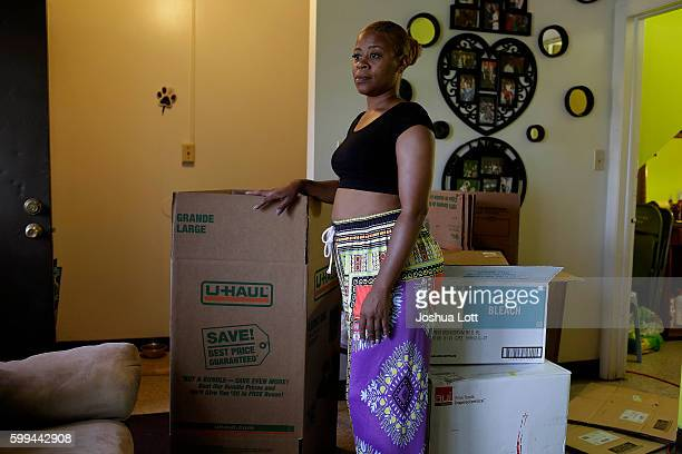 Tonona Parker stands next to a moving box she received from the United States Environmental Protection Agency as she poses for a portrait inside her...