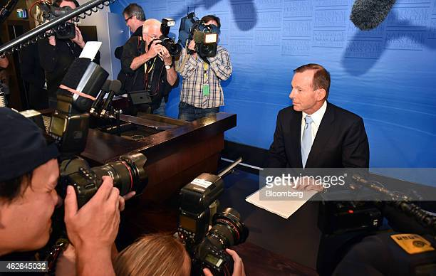 Tony Abbott Australia's prime minister right poses for members of the media before delivering a speech at the National Press Club in Canberra...